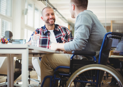 man-in-wheelchair-talking-to-friend-at-table_485x342